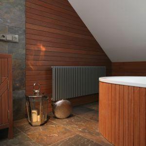 Łazienka pod skosami zwraca uwagę doborem materiałów - naturalnego kamienia i drewna w ciemnych odcieniach. Fot. Bartosz Jarosz