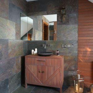 Narożne lustro w strefie umywalkowej sprawia, że wnętrze wydaje się jeszcze większe. Blat drewnianej szafki podumywalkowej stanowi dodatkową powierzchnię do ustawienia świec lub olejków zapachowych.  Fot. Bartosz Jarosz