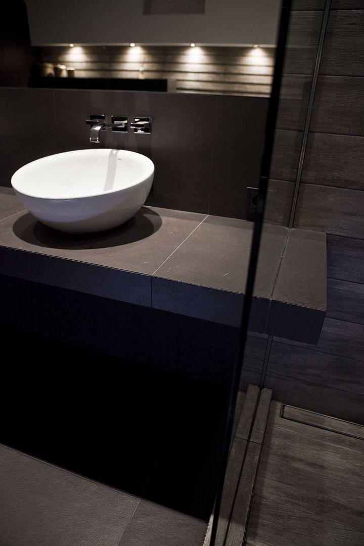 """Podumywalkowy blat """"przecina"""" taflę szkła oddzielającą strefę prysznica od reszty pomieszczenia. Połączenie dwóch części blatu dało wyjątkowy efekt wizualny oraz praktyczny w postaci półki na kosmetyki pod prysznicem. Odpływ liniowy Wiper Premium Pure, deszczownica Blue Water. Fot. Michał Łuczak"""