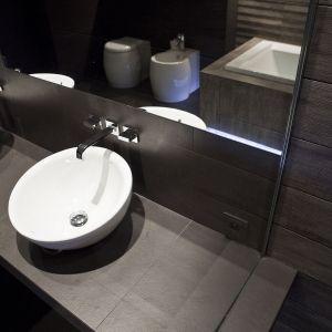 Na wykończonym płytkami gresowymi blacie ustawiono dwie umywalki w kształcie mis (Roca Bol); dobrano do nich podtynkowe baterie Level marki Paffoni .Fot. Michał Łuczak