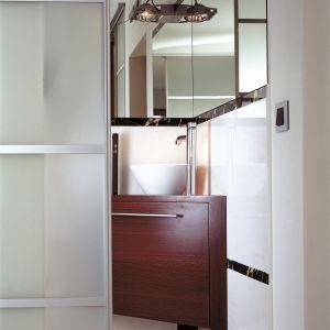 Białą umywalkę w formie klasycznej misy ustawiono na szafce-postumencie wpisanym w narożnik pomieszczenia dokładnie naprzeciw drzwi. Fot. Paweł Supernak