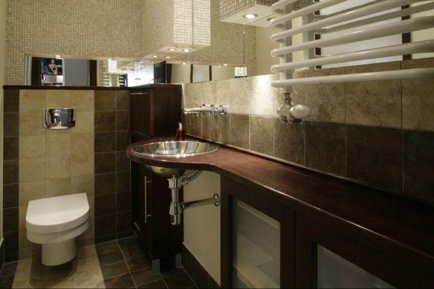 Toaleta gościnna oraz sąsiadująca z nią kuchnia dzielą się światłem. Przez mleczne szkło oprawione w ramę o wysokości równej wysokości ściany przenika światło z kuchni i na odwrót.