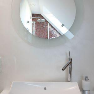 Okrągłe lustro nad umywalką dodaje nieco przestrzeni, odbijając okno dachowe i strefę prysznica.  Fot. Bartosz Jarosz