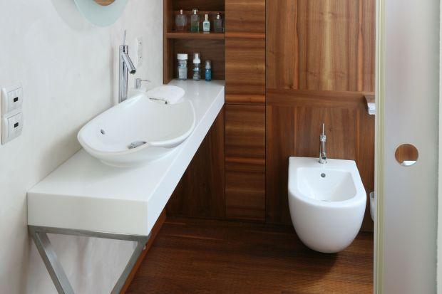 Drewno w ciepłej barwie doskonale nadaje się nawet do ułożenia strefie prysznica. W tej małżeńskiej łazience naturalny materiał doskonale ociepla eleganckie wnętrze.