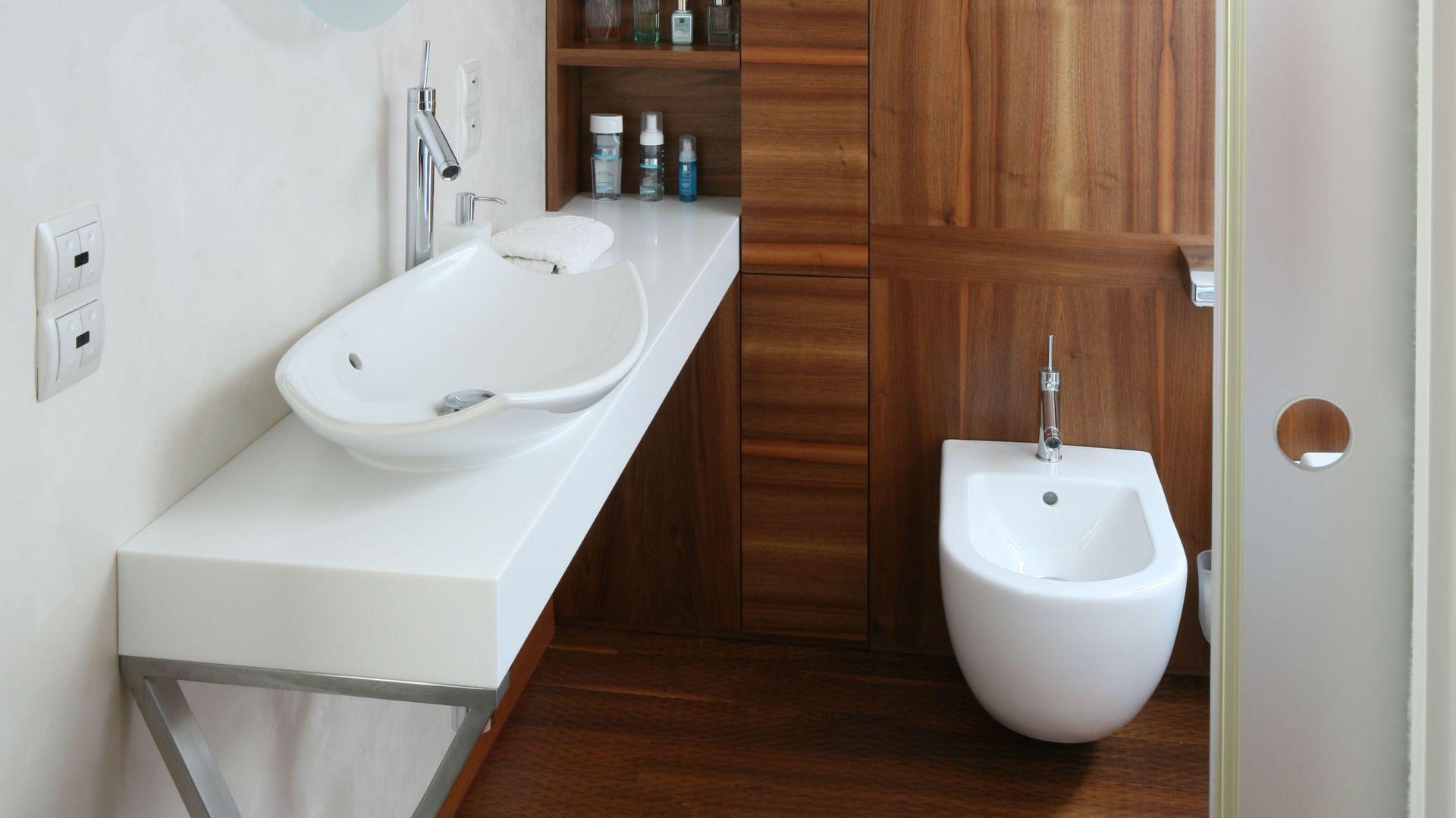 Białe ściany zostały wykończone odpornym na wilgoć tynkiem dekoracyjnym, naturalne drewno dodaje łazience przytulnego klimatu. Fot. Bartosz Jarosz