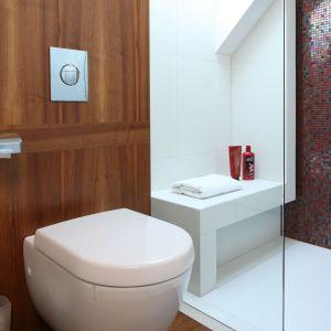 Drewno nadaje łazience bardzo ciepły, pokojowy charakter, a szklana mozaika mieniąca się odcieniami fioletu, niczym biżuteria, pięknie dekoruje jedną ze ścian pod prysznicem. Fot. Bartosz Jarosz