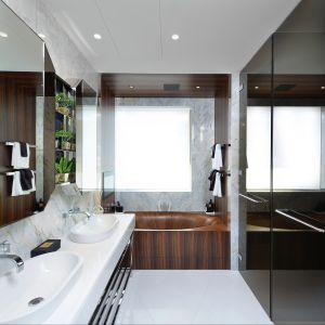 """Łazienka w """"Honky Apartment"""" w pokazowym mieszkaniu kompleksu One Tower Bridge. Lustrzane, błyszczące powierzchnie (lustra oraz drzwiczek) korespondują z marmurową okładziną ścienną. Wannę wykonano z drewna orzechowego, posiada jedwabiste, lśniące wykończenie."""