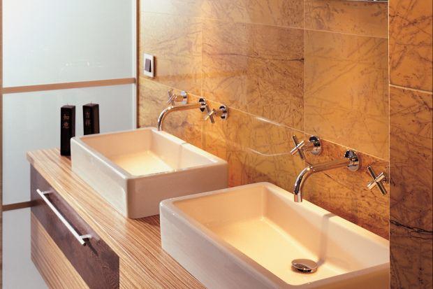 Podłoga i ściany w tej łazience wyłożono marmurem Amarillo Triana przypominającym skamieniałe drewno. Całość tworzy klimat r&oacute;wnowagi i harmonii. <br /><br />