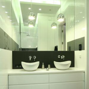 Nowoczesnej, ubranej w achromatyczne barwy łazience  szyku dodają elementy glamour, m.in. srebrne, wiszące lampy oraz akcesoria łazienkowe. Podobnie jak styl Hepburn projekt wnętrza cechuje powściągliwa elegancja. Fot. Bartosz Jarosz