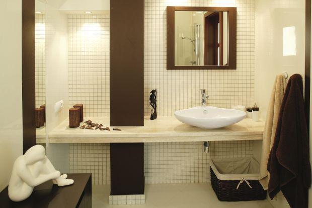 Dominujące w aranżacji łazienki delikatne odcienie ecru i ciemnobrązowe akcenty tworzą smakowite zestawienie, niczym śmietanka przyprószona czekoladą.