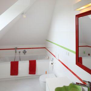 Kolorowa i wesoła łazienka dla dziecka zaprojektowana jest na bazie białych okładzin. Ożywiają ją czerwone listwy ceramiczne, czerwone dodatki i kolorowa umywalka. Proj. Katarzyna Merta-Korzniakow. Fot. Bartosz Jarosz