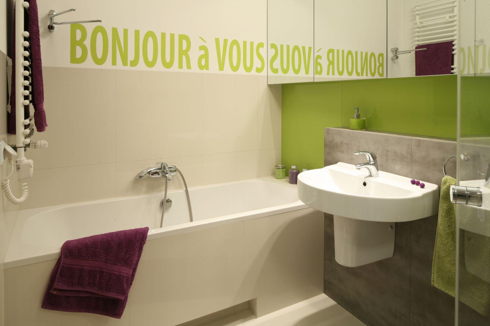 Fragmenty ścian pomalowano farbą w odcieniu seledynowym i fioletowym - pod kolor zostały dobrane także ręczniki. Proj. Marta Kruk . Fot. Bartosz Jarosz