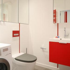 Czerwona szafla pod umywalkę, a do tego czerwone pionowe listwy dekorują okładzinę z białych płytek. Proj. Iza Szewc. Fot. Bartosz Jarosz