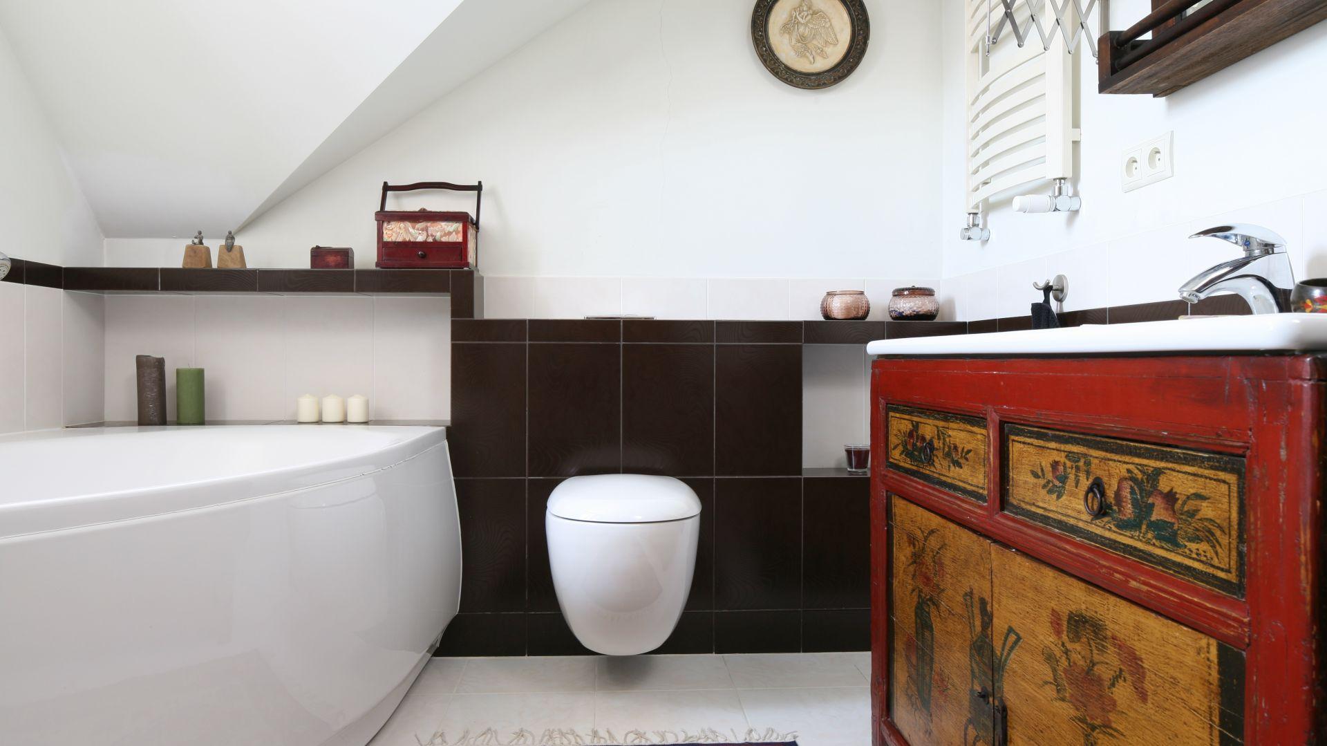 Łazienka na piętrze domu, pod skosami dachowymi, to wnętrze zaprojektowane dla całej rodziny. Szafka podumywalkowa to mebel kupiony w sklepie ze starociami. Fot. Bartosz Jarosz