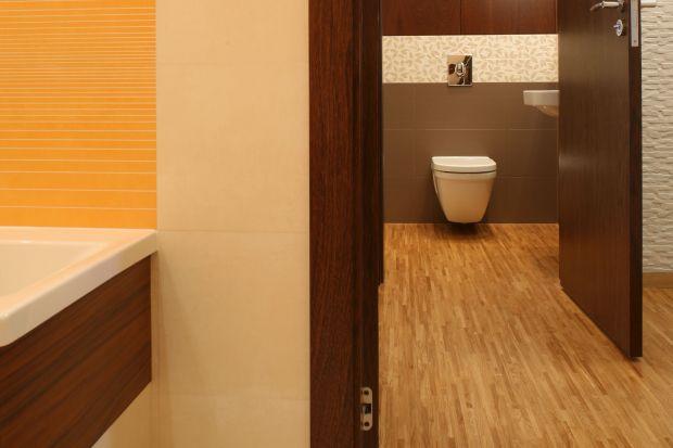 Drewno w tej łazience pojawia się w kilku odcieniach i gatunkach: na parkiecie polski jesion, na frotach szafek łazienkowych egzotyczna sucupira.