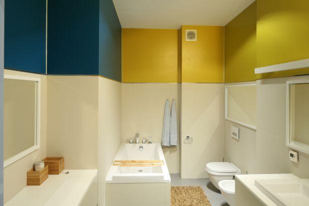 W tej łazience dla rodziny rządzi dobry design, lustra oraz pogodne kolory. Ściany pomalowane zostały farbą odporną na wilgoć, ale w bardzo nietypowy sposób. Kolorowy jest tylko pas usufitu.