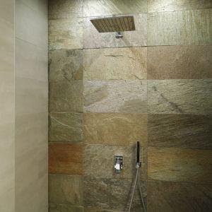Otwarta wnęka prysznicowa została wykończona pięknym kamieniem, dlatego każda kąpiel będzie tutaj miała orzeźwiający charakter. Komfort zapewnia rączka prysznicowa i duża kwadratowa głowica deszczowa.Proj. Piotr Stanisz. Fot. Bartosz Jarosz