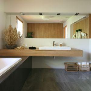 Całe pomieszczenie utrzymane jest w jednolitej stylistyce. Na podłodze w obu strefach oraz obudowie wanny – polerowany, grafitowy gres. Fot. Bartosz Jarosz