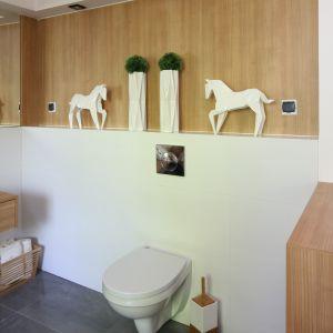 Wykończona płytą meblową oraz podświetlona wnęka nad sedesem (Cersanit) pełni funkcję dekoracyjną, a jej lustrzane odbicie optycznie powiększa łazienkę. Ściany do połowy wysokości wykończone białą glazurą. Fot. Bartosz Jarosz
