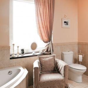 Zasłona i tapicerka fotela wykonane są z tej samej tkaniny. Charakter łazienki podkreślają stylowe akcesoria. Fot. Bartosz Jarosz