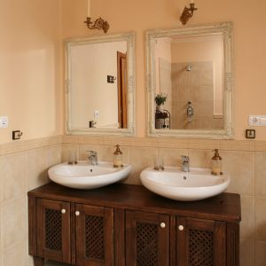 Piękną dekoracją łazienki są lustra w rzeźbionych ramach. Nad nimi zainstalowano kinkiety ze świecami. Fot. Bartosz Jarosz