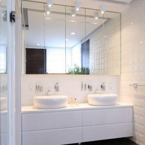 Białą łazienkę wyposażono w dyskretne lampki zamontowane w strefie umywalek. Proj. Katarzyna Mikulska-Sękalska. Fot. Bartosz Jarosz