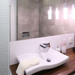Wiszące lampki dodają szarej łazience ciepłego klimatu. Proj. Karolina Łuczyńska. Fot. Bartosz Jarosz