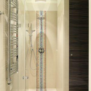 W łazience do dyspozycji użytkowników jest także prysznic we wnęce zamkniętej szklanymi drzwiami. Pięknie dekoruje wnękę mozaika, której pas przechodzi dokładnie przez środek - w tym miejscu zainstalowano deszczownicę i baterię podtynkową (na ścianie) oraz odpływ punktowy (w posadzce). Fot. Bartosz Jarosz