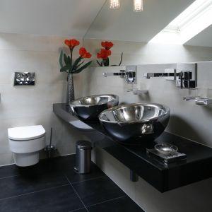 Lustro nad umywalkami zajmuje całą szerokość ściany; jego format dopasowano do nachylenia skosu. Fot. Bartosz Jarosz