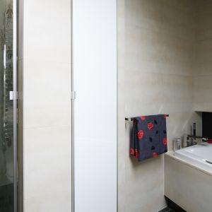 Łazienka jest przestronna i zachowuje elegancki wygląd, ponieważ wszystkie drobiazgi zostały ukryte w szafce wnękowej zamkniętej wysokim frontem.  Fot. Bartosz Jarosz