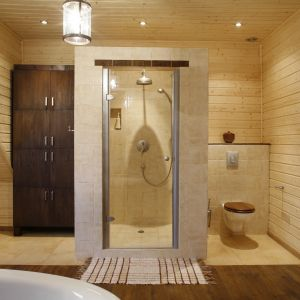 Po obu stronach wysuniętej do środka łazienki kabiny prysznicowej powstały funkcjonalne aneksy. W jednym umieszczono sedes, w drugim wysoką szafę m.in. na ręczniki. Fot. Bartosz Jarosz