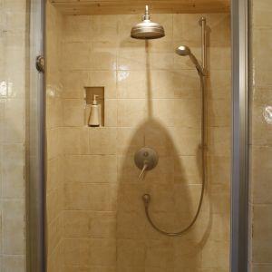 Wnękę prysznicową zamyka się drzwiami ze szkła. Wykończono ja płytkami z efektem postarzenia i drewnem. Fot. Bartosz Jarosz