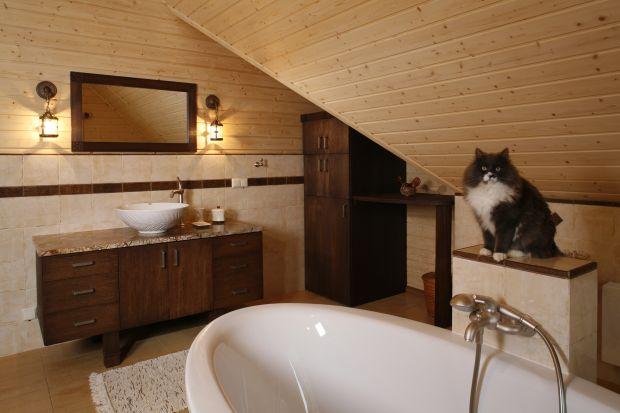 Jak przystało na salon kąpielowy, jego centrum zajmuje wolno stojąca wanna. I – jak przystało na zagubioną wśród mazurskich bezdroży rezydencję z bali – wypełnia go zapach świerkowego drewna.