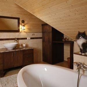 Łazienka w domu z bali ma wyjątkowy klimat. Szafka,wstawiona we wnękę pod skosem, w swej dolnej części ukrywa... pralkę. Fot. Bartosz Jarosz