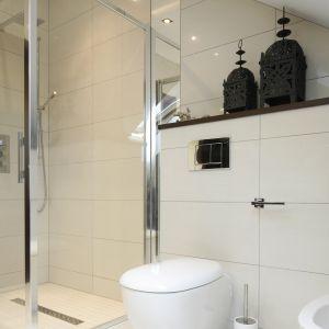 Kabina prysznicowa została zamontowana bezpośrednio na posadzce wykończonej w tym miejscu beżową mozaiką. Odprowadzenie wody gwarantuje odpływ liniowy z dekoracyjnym, stalowym przykryciem.  Fot. Bartosz Jarosz