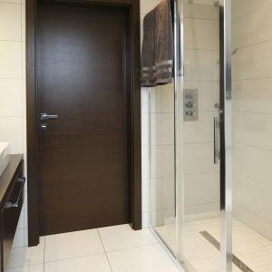 Narożna kabina prysznicowa oferuje sporo miejsca do kąpieli, a przesuwane drzwi umożliwiają łatwe i wygodne wejście. Wyposażono ją w podtynkową baterię, prostokątną głowicę deszczową i rączkę prysznicową.  Fot. Bartosz Jarosz