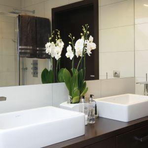 Pan i pani domu mogą korzystać z łazienki jednocześnie - lustro zajmuje całą szerokość ściany, a na blacie jest dużo miejsca na osobiste drobiazgi.  Fot. Bartosz Jarosz