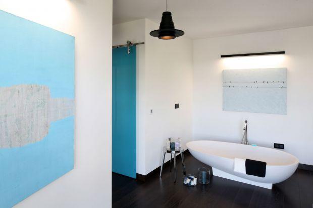Toaleta przy sypialni ma artystyczny klimat loft. Zlokalizowana jest w apartamencie pokazowym na warszawskim Mokotowie.Płynnie łączy się z sypialnią - w niej ustawiono bowiem komfortową wannę!