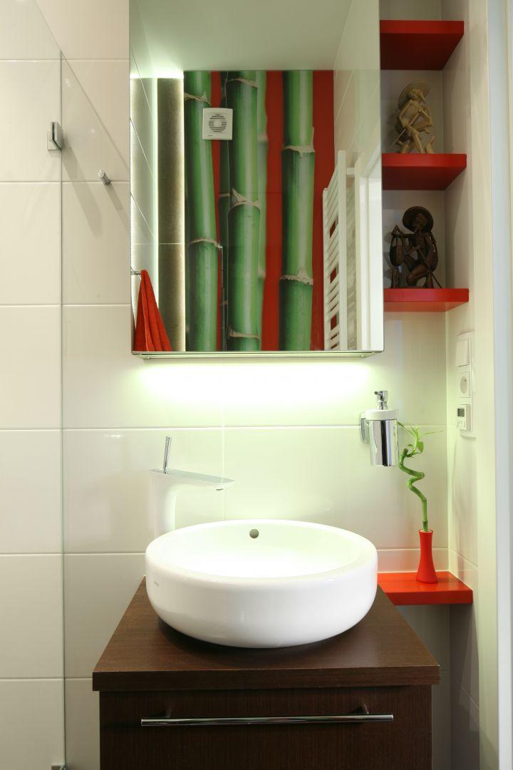 Dzięki czerwonym akcentom, aranżacja łazienki gościnnej ma wyrazisty charakter. W tym kolorze są m.in. półeczki obok umywalki przeznaczone na dekoracje. Fot. Bartosz Jarosz