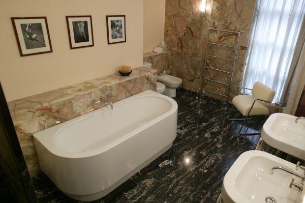 To łazienka w kamieniu znajdująca się przy sypialni. Niezwykle elegancka, ponadczasowa i przytulna. Zachwycają onyks oraz marmur.
