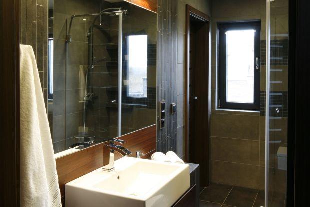 W tej łazience wszystko służy optycznemu powiększeniu przestrzeni. Poziome pasy z płytek, mozaika z małych prostokątów, lustra...