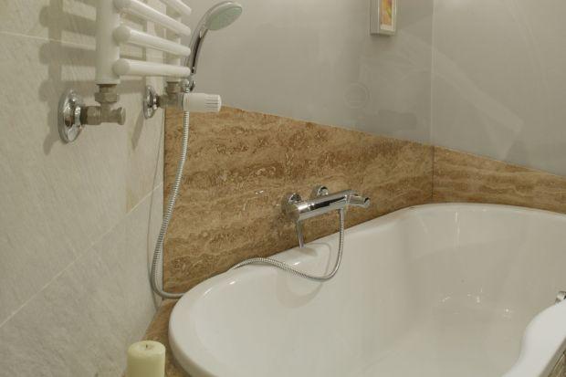 Rolę główną gra tu komfortowa wanna w pięknej obudowę z naturalnego kamienia. Jego ciepłe odcienie beżu i brązów sprawiają, że łazienka wydaje się elegancka, ale i przytulna.