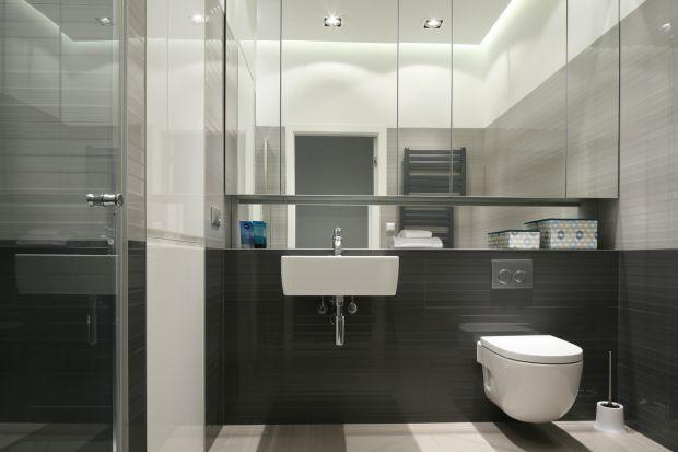 Łazienka urządzona w szarościach utrzymana jest wnieco chłodnym, minimalistycznym stylu. Klimat zmienia się w strefie prysznica za sprawą fototapety z motywem drapaczy chmur.