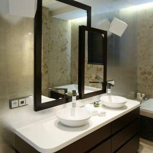 Dwie umywalki oraz lustra tworzą oddzielny kącik dla każdego z rodzeństwa. Połyskliwa ściana została obłożona szlagmetalem w kolorze srebra. Fot. Bartosz Jarosz