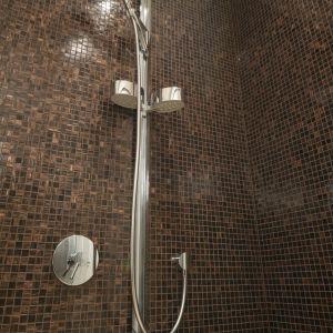 Ścianę w strefie prysznica obłożono połyskliwą mozaiką. Długi uchwyt pozwala, odpowiednio do wzrostu użytkownika, regulować wysokość słuchawki prysznicowej. Fot. Bartosz Jarosz
