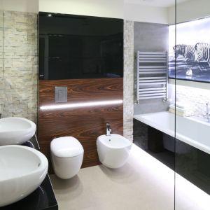 Oświetlenie w postaci dekoracyjnych pasów zastosowano w kilku miejscach w łazience, m.in. nad sanitariatami oraz wokół obrazu nad wanną. Proj. Małgorzata Mazur. Fot. Bartosz Jarosz