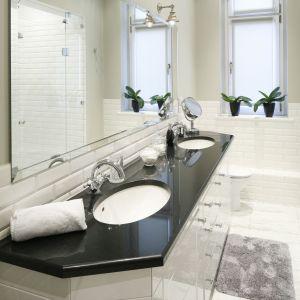 Wąska biała łazienka ma elegancki blat z ciemnego granitu. Proj. Iwona Kurkowska. Fot. Bartosz Jarosz