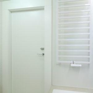 Biały grzejnik jest niemal niewidoczny na tle jasnej ściany. Fot. Bartosz Jarosz