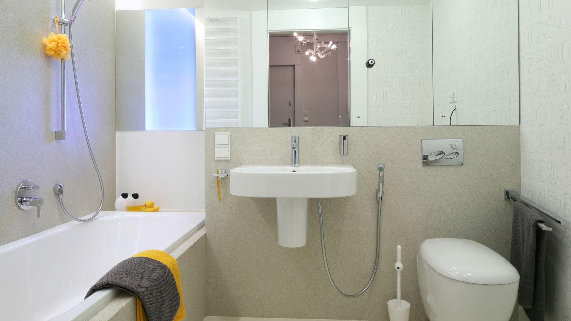 Jasną łazienkę optycznie powiększa szafka w lustrzanymi frontami. Na ścianach ułożono duże płytki w formatach 60x120 cm, dzięki czemu całość wygląda bardzo estetycznie. Fot. Bartosz Jarosz