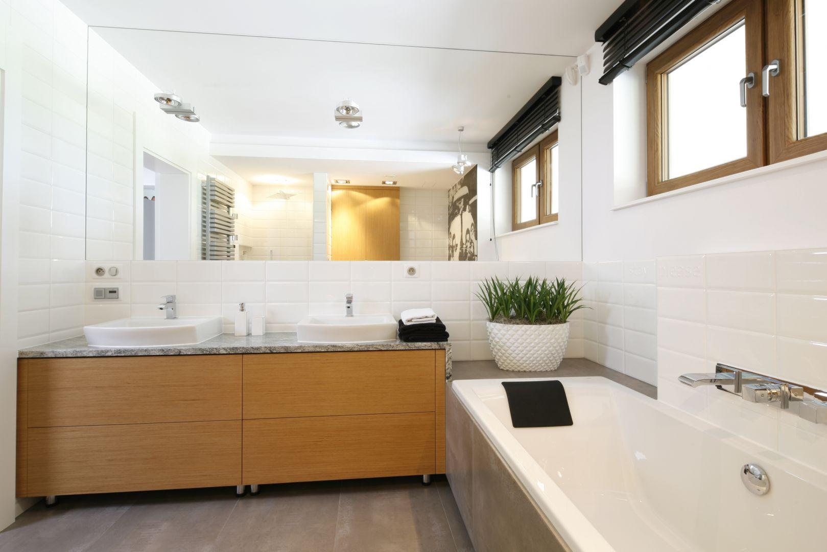 Optyczne powiększenie zapewnia łazience ogromna tafla lustra. Dwie umywalki gwarantują wygodę codziennej toalety. Zamontowano je z myślą o dwójce nastolatków. Fot. Bartosz Jarosz